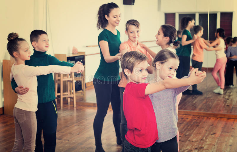 Children studying of partner dance at dance school. Happy cheerful positive children studying of partner dance at dance school stock image