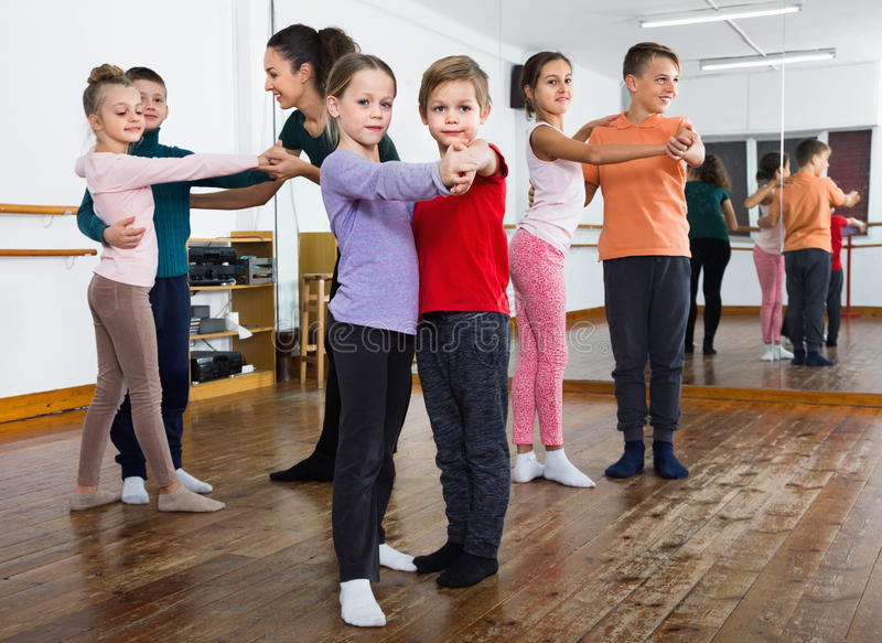 Children studying of partner dance at dance school. Happy glad children studying of partner dance at dance school royalty free stock image