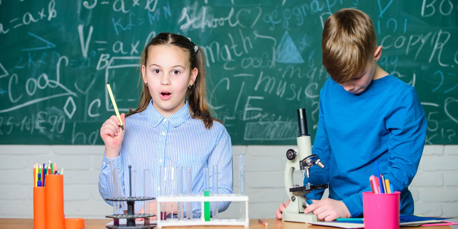 Children studying together classroom. School education. Chemical analysis. Kids study chemistry. School chemistry lesson. School laboratory. Girl and boy royalty free stock photos