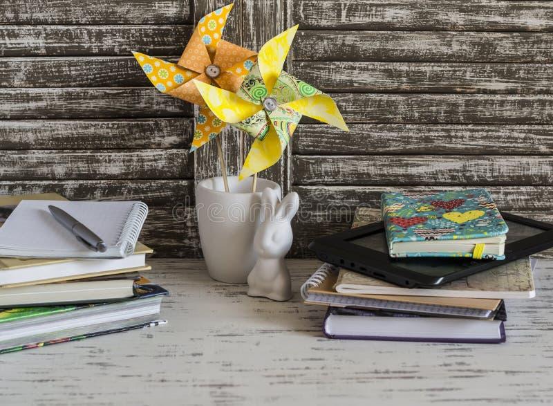 Children stwarzają ognisko domowe workspace z książek, notatników, notepads, pastylki i handmade papieru pinwheels, fotografia stock