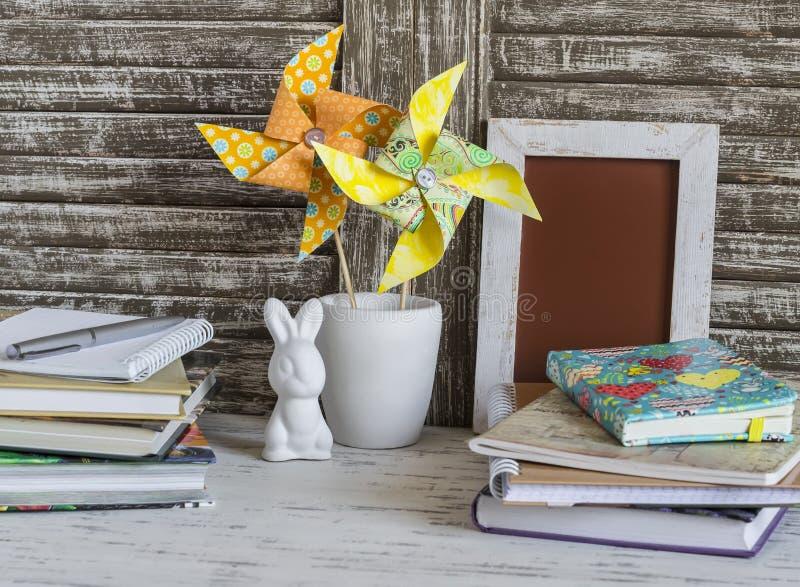 Children stwarzają ognisko domowe workspace z książkami, notatnikami, notepads, handmade papieru pinwheels i Easter królikiem, fotografia royalty free