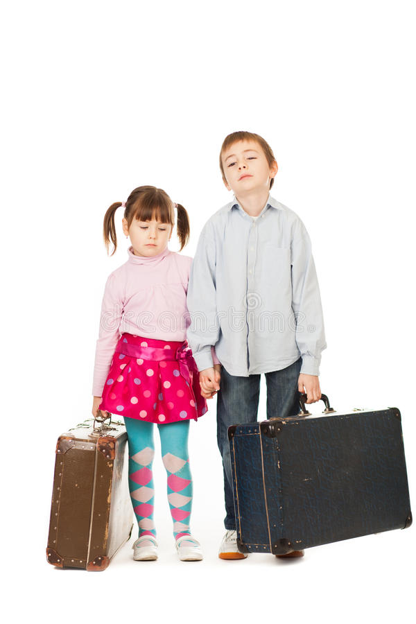 Children with suitcases. Two bored young children with retro suitcases, white background stock photos