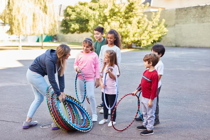 Children in summer camp with sports teacher. During physical education with hoops stock images