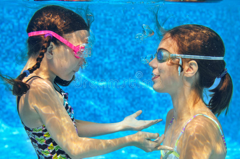 Children swim in pool underwater, girls in goggles have fun. Children swim in pool underwater, happy active girls in goggles have fun in water, kids sport on stock images