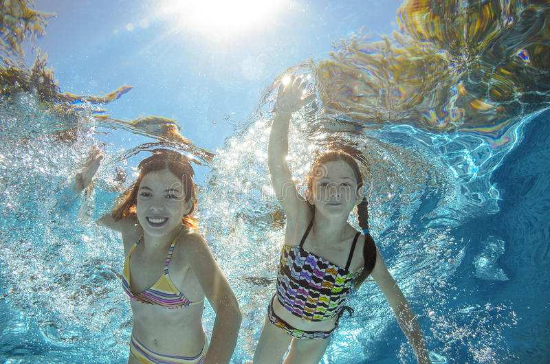 Children swim in pool underwater, girls have fun in water. Children swim in pool underwater, happy active girls have fun in water, kids sport on family vacation stock photos