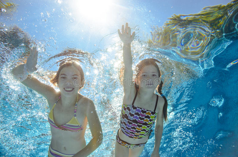 Children swim in pool underwater, girls have fun in water. Children swim in pool underwater, happy active girls have fun in water, kids sport on family vacation stock photography
