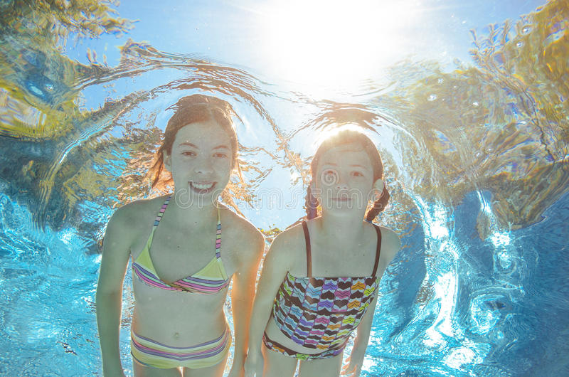 Children swim in pool underwater, girls have fun in water. Children swim in pool underwater, happy active girls have fun in water, kids sport on family vacation stock photo
