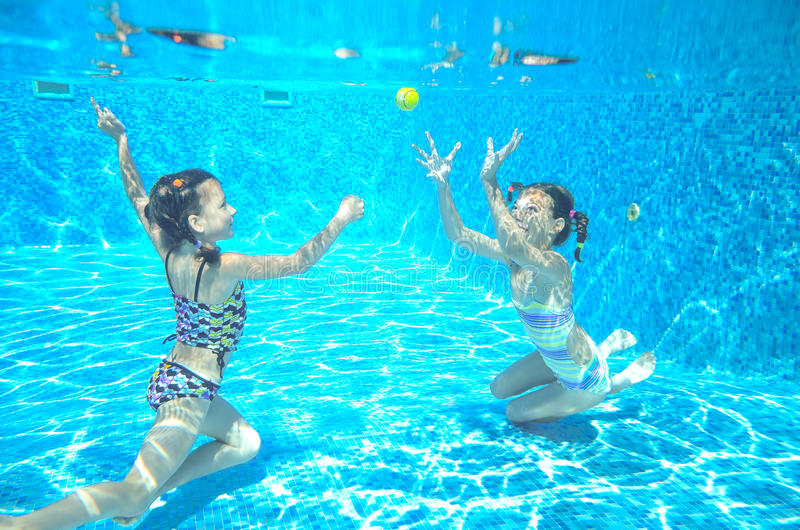 Children swim in pool underwater, girls have fun in water,. Children swim in pool underwater, happy active girls have fun in water, kids sport on family vacation stock image