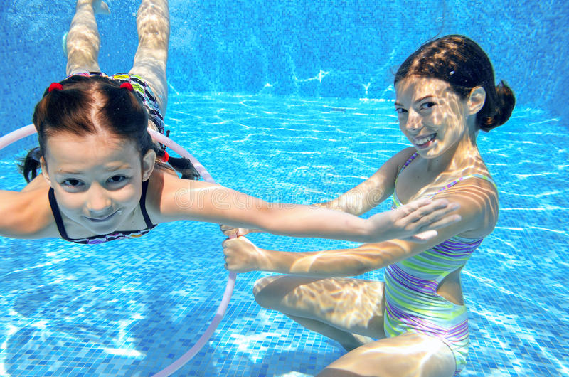 Children swim in pool underwater, happy active girls have fun under water, kids sport. On family vacation stock images