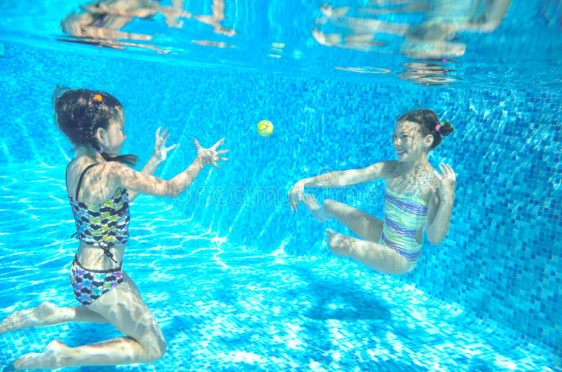 Children swim in pool underwater, happy active girls have fun under water, kids sport. On family vacation royalty free stock images