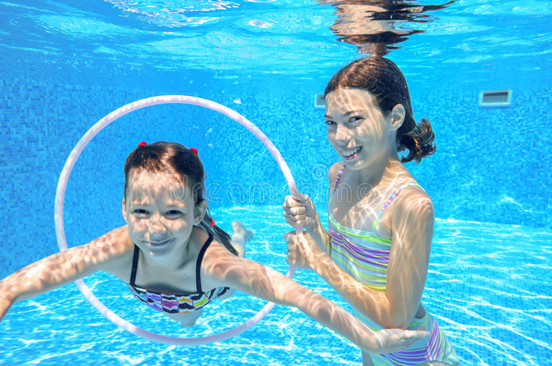 Children swim in pool underwater, happy active girls have fun under water. Kids sport on family vacation royalty free stock images