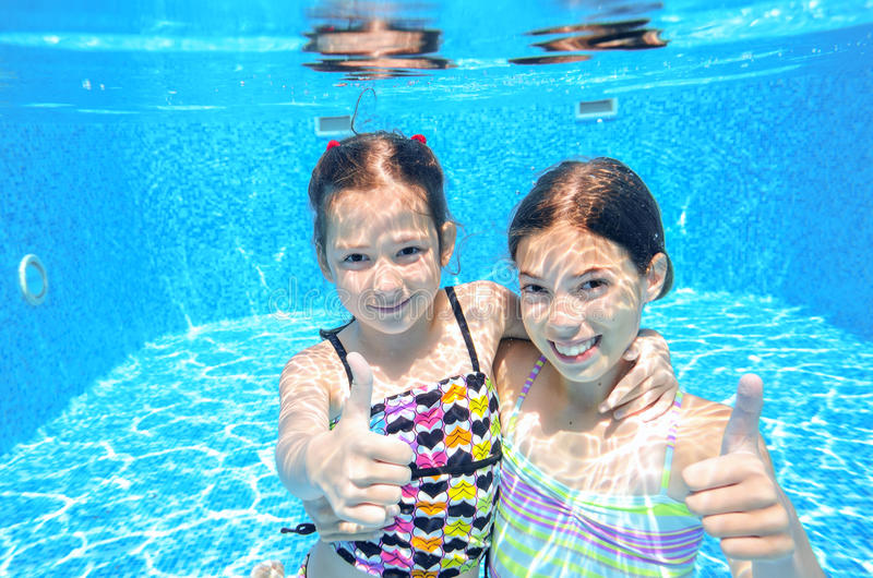 Children swim in pool underwater. Happy active girls have fun in water, kids sport on family vacation royalty free stock photos