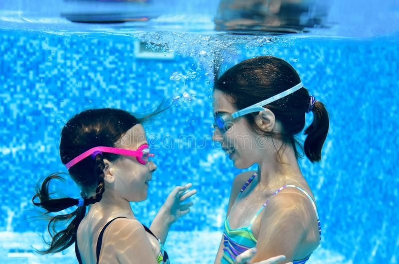Children swim in swimming pool underwater, happy active girls have fun under water, kids fitness and sport. On active family vacation royalty free stock image