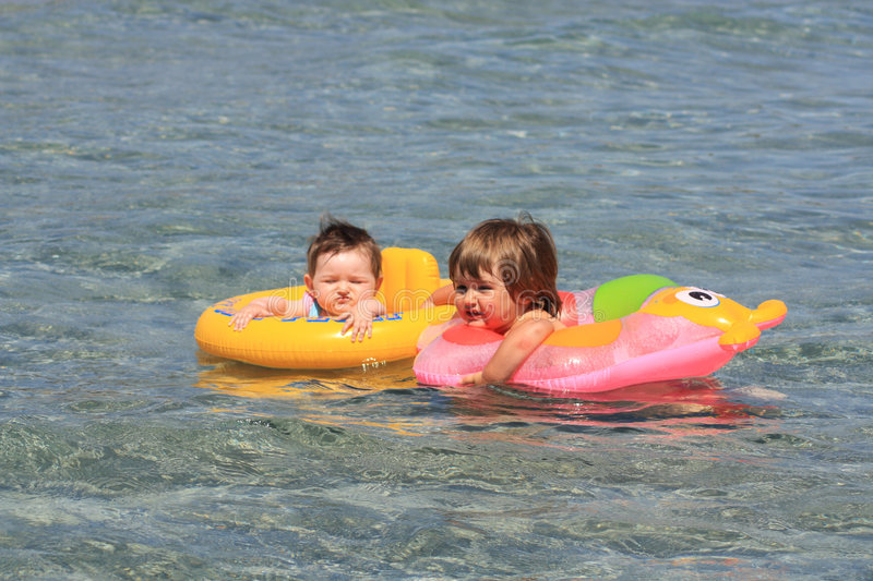 Children swimming. With a safety vests stock photos