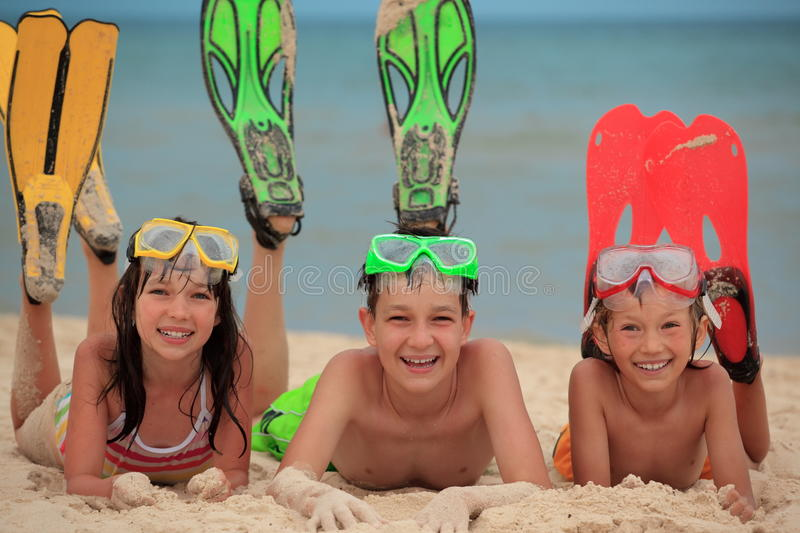 Children with swimming fins. Happy, smiling children with swimming fins and goggles, lying on a sandy beach royalty free stock photos