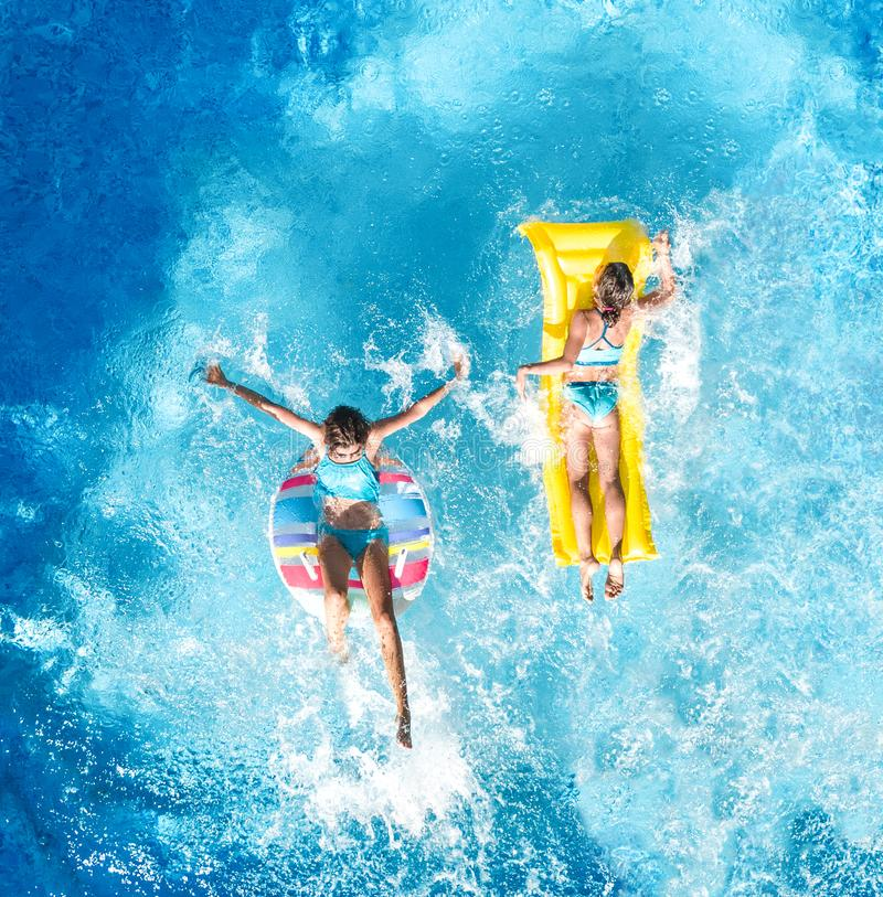 Children in swimming pool aerial drone view fom above, happy kids swim on inflatable ring donut and mattress, girls have fun. Children in swimming pool aerial royalty free stock photography