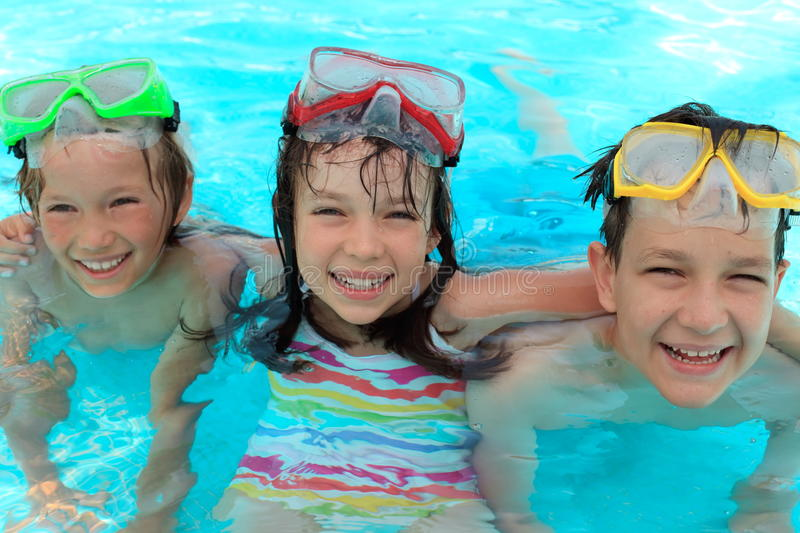 Children in swimming pool. Three happy, smiling children with goggles, in the water of a swimming pool royalty free stock images