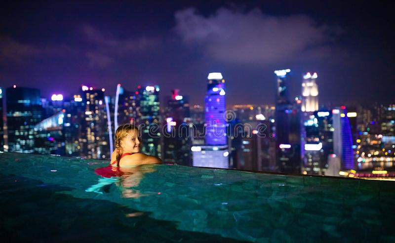 Children swimming in roof top outdoor pool on family vacation in Singapore. City skyline from infinity pool in luxury hotel. Kids stock images