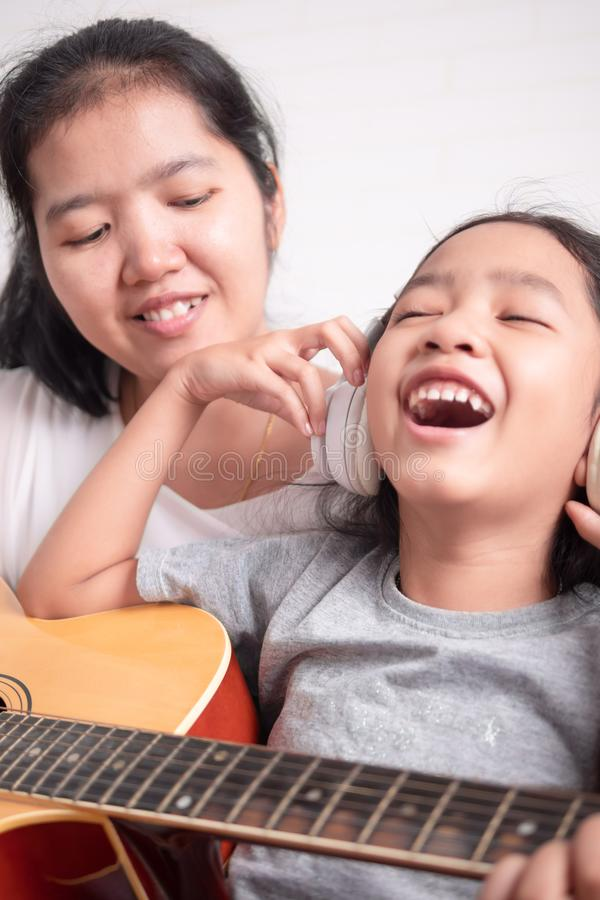 Children take a headphone and laugh with happiness. Mom is teaching her daughter to play guitar. Asian little girl learning to play music. Children take a royalty free stock image