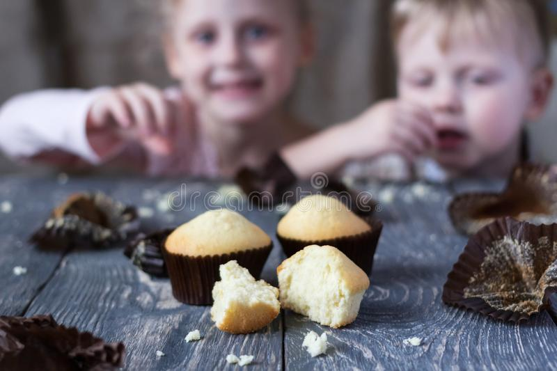 Children taste finished cupcakes sitting behind wooden surface stock photography
