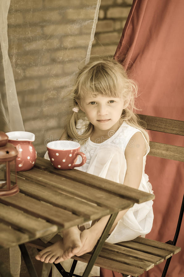 Children tea time. Beautiful girl with long hair during tea time filtered effect stock photos