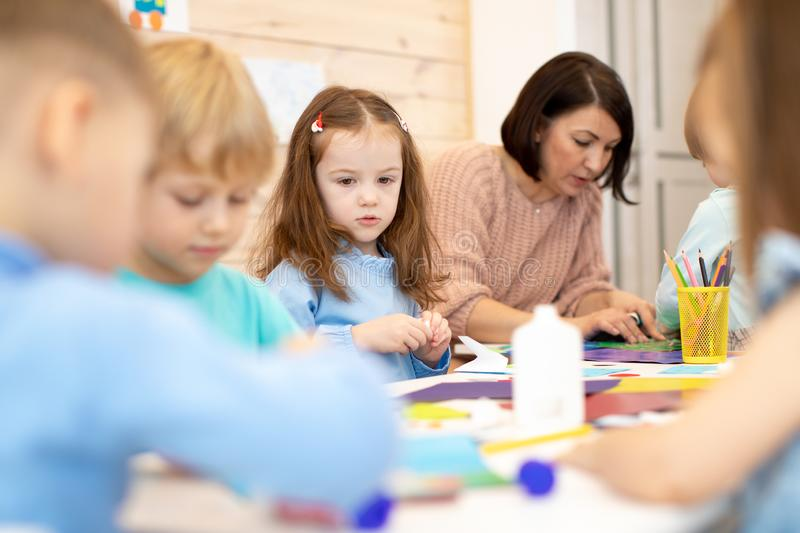 Children with teacher in classroom. Group of children doing project in kindergarten. Kids hands crafting into team. royalty free stock images