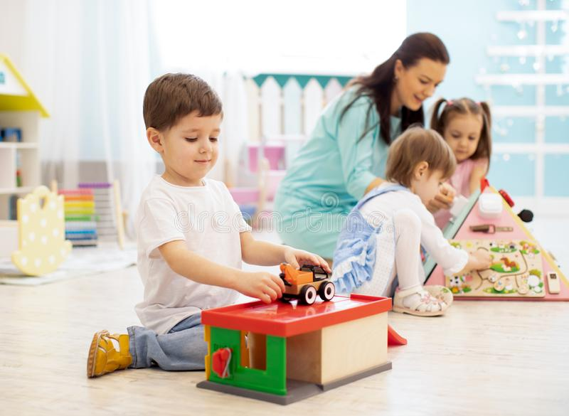 Children with teacher in daycare. Kids play with toys in kindergarten. Little boy playing with car and parking garage. royalty free stock images