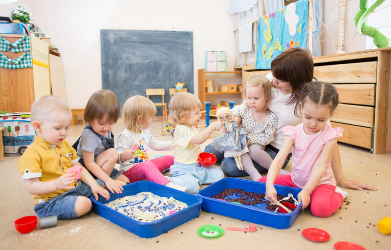 Children with teacher improving hands motor skills in kindergarten. Group of children and nurse playing with rice and beans in kindergarten or day care centre royalty free stock photos