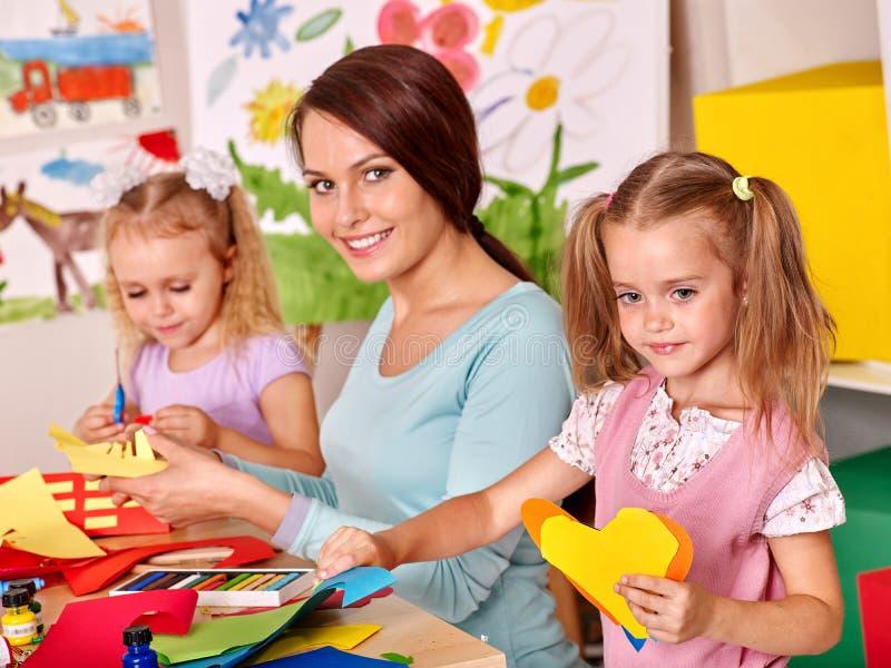 Children with teacher painting stock photo