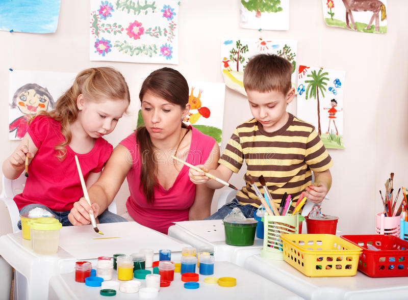 Children with teacher painting play room. stock photos