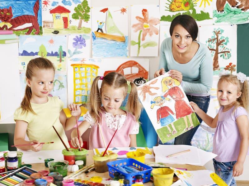 Children with teacher at school. stock image