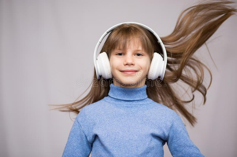 Children and technology concept - smiling girl with headphones listening to music isolated on white. Long hair flying from moving stock photos