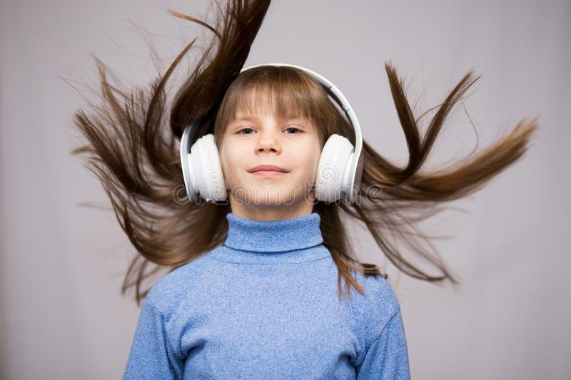 Children and technology concept - smiling girl with headphones listening to music isolated on white. Long hair flying royalty free stock images