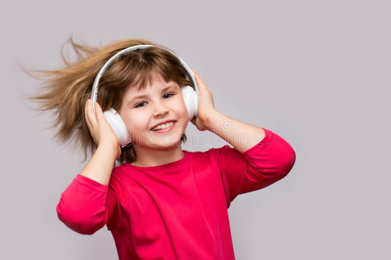 Children and technology concept - smiling girl with headphones listening to music isolated on white. Long hair flying from moving royalty free stock image