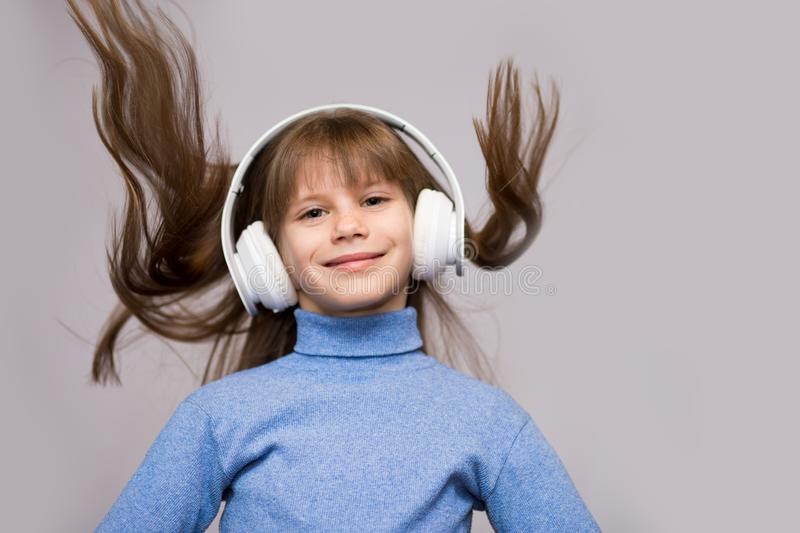 Children and technology concept - smiling girl with headphones listening to music isolated on white. Long hair flying. From moving stock photos