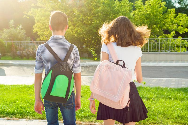 Children teenagers go to school, back view. Outdoors, teens with backpacks. stock image