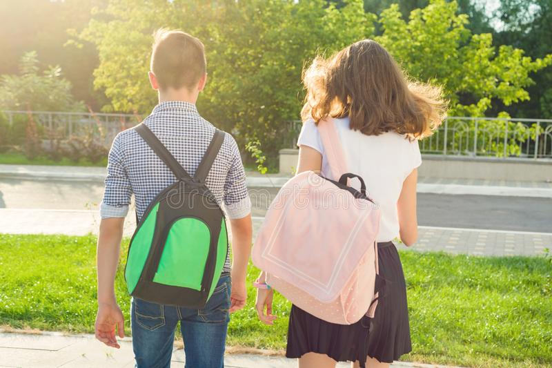 Children teenagers go to school, back view. Outdoors, teens with backpacks stock photos