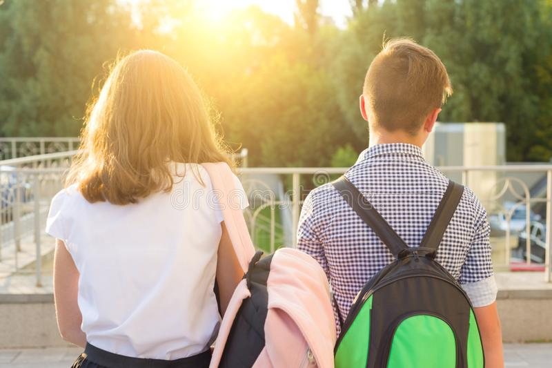 Children teenagers go to school, back view. Outdoors, teens with backpacks stock photo