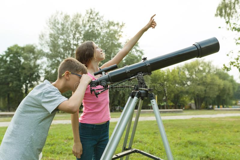 Children teenagers with telescope look at the sky in nature royalty free stock photo