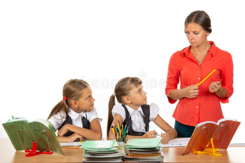 Children at their desks look at the angry teacher with fear stock image