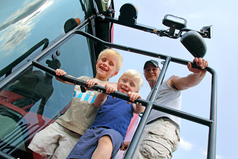 Children and Their Father Smiling as the Climb a Farm Tractor. A happy family of two young children and their father are smiling as they climb up the ladder of a stock image