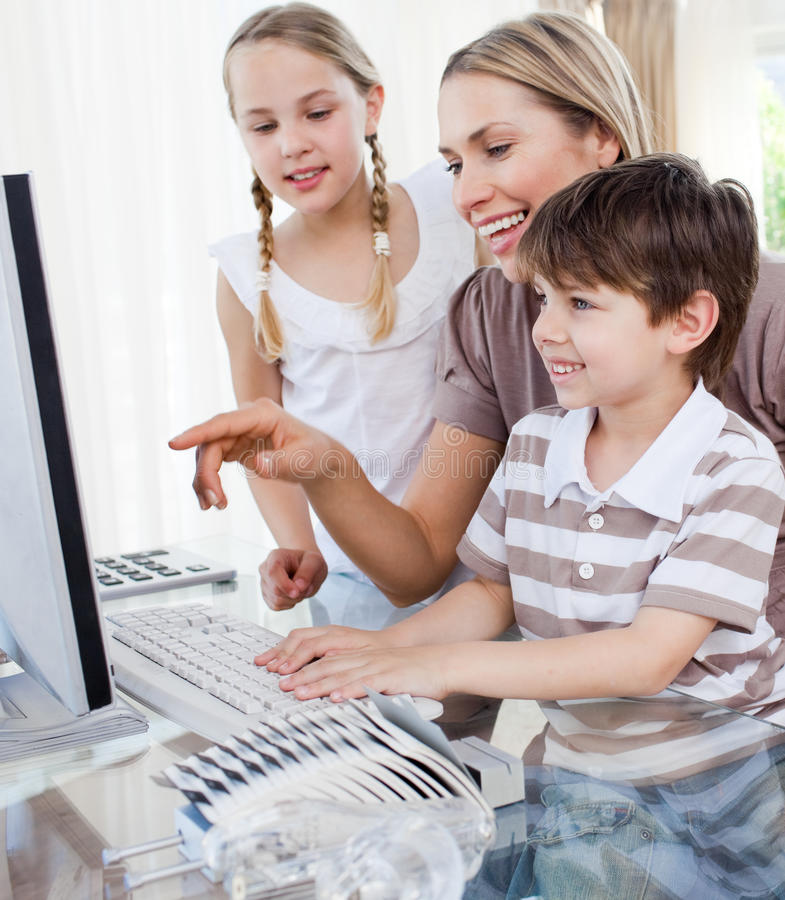 Children and their mother using a computer royalty free stock photo