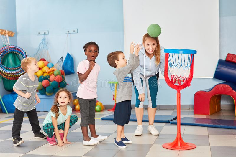 Children throw basketball into a net. In the gym in kindergarten or preschool royalty free stock photography