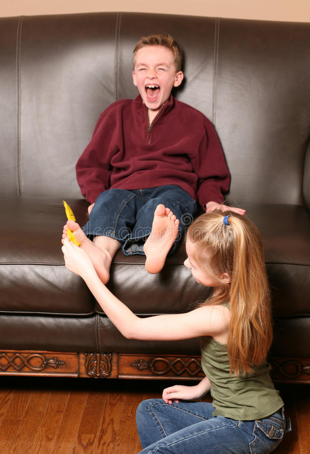 Free Children Tickling Feet With Feather Stock Photo - 21165740