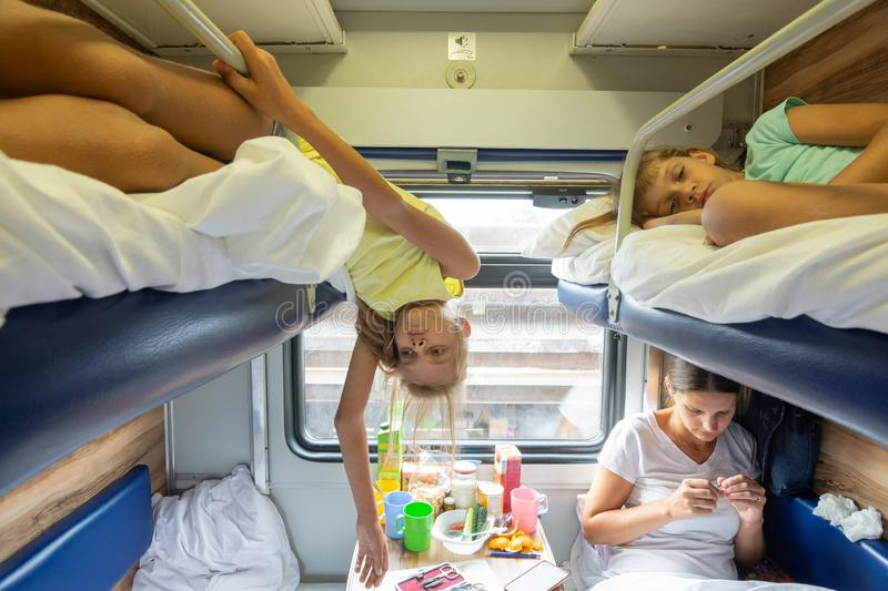Children are tired of riding in a reserved seat train car without air conditioning for a long time. Children are tired of riding in a reserved seat train car stock image
