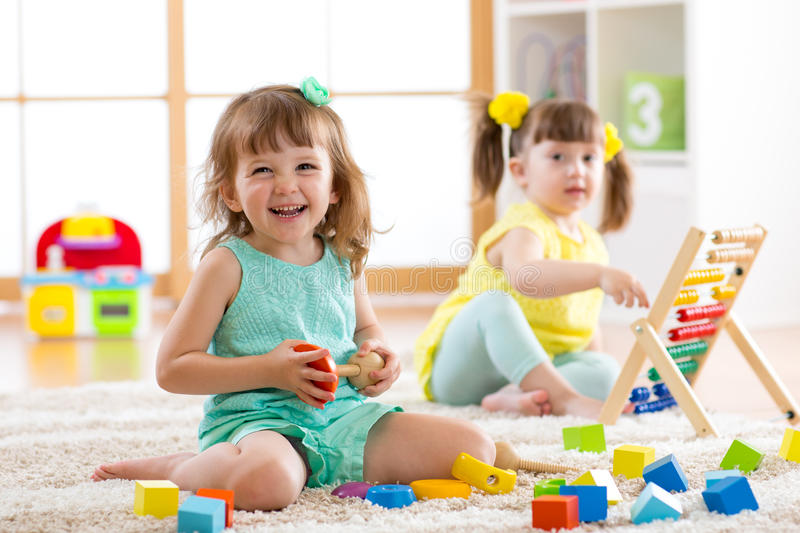Children toddler and preschooler girls play logical toy learning shapes, arithmetic and colors in kindergarten or stock image