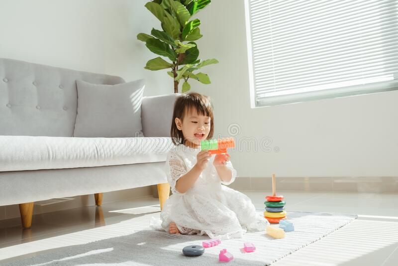 Children toddlers girls play logical toy learning shapes, arithmetic and colors at home.  stock image