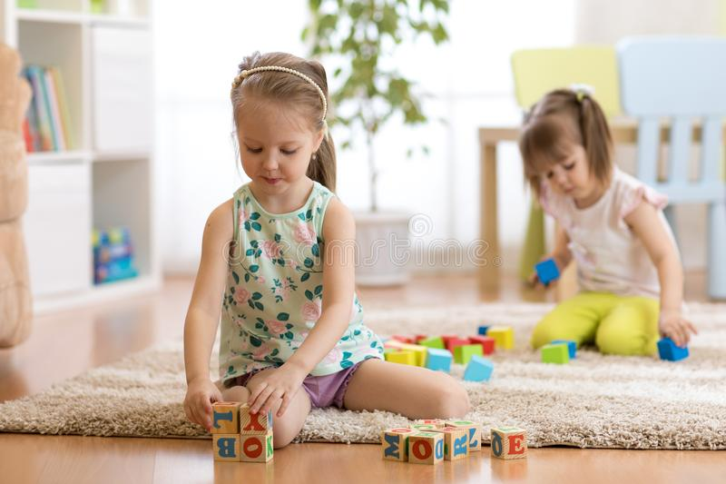 Children toddlers girls play toys at home, kindergarten or daycare centre. stock photos