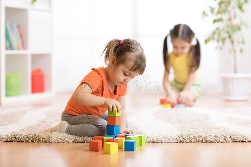Children toddlers girls playing toys at home, kindergarten or nursery stock photo