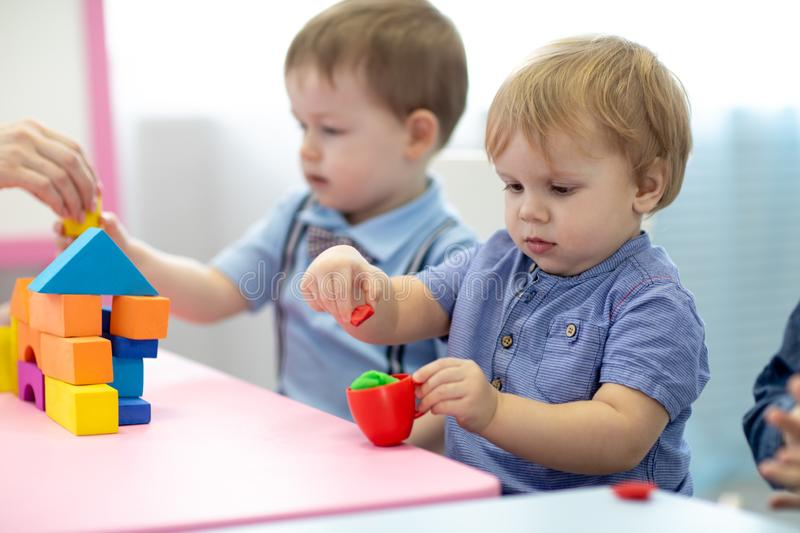 Children toddlers play colorful clay toy in kindergarten royalty free stock photos